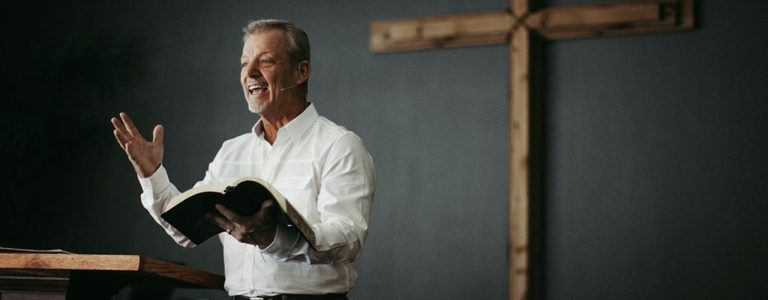 Pastor reading from bible during sermon